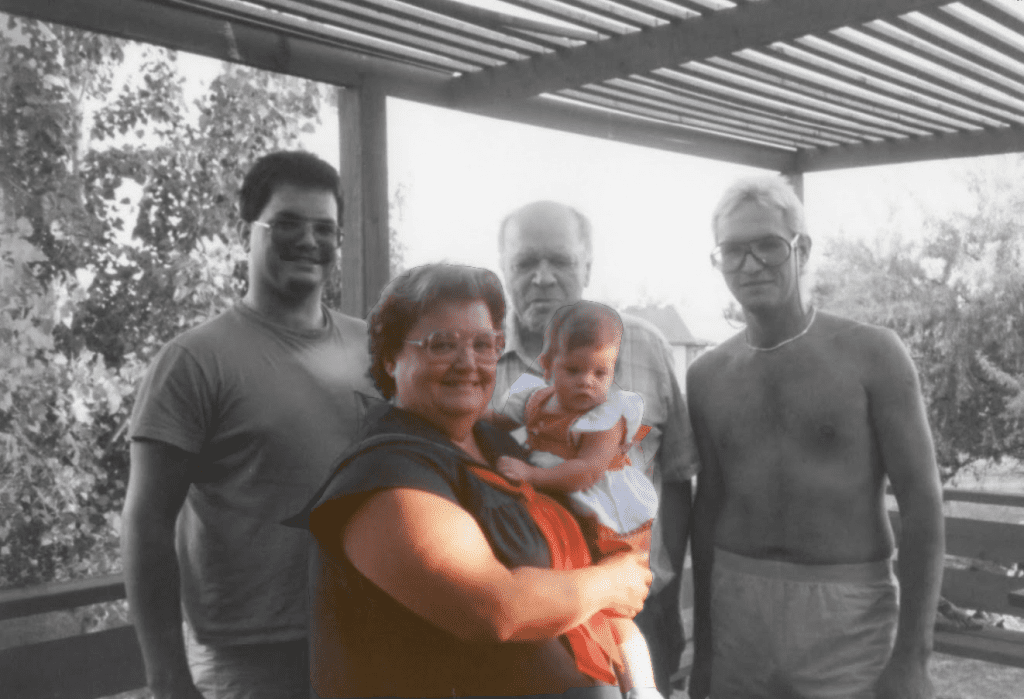 Photo: Rachel's family - from left: father, Grandma is holding Rachel and they are in color, grandpa and uncle (the men are in black and white)